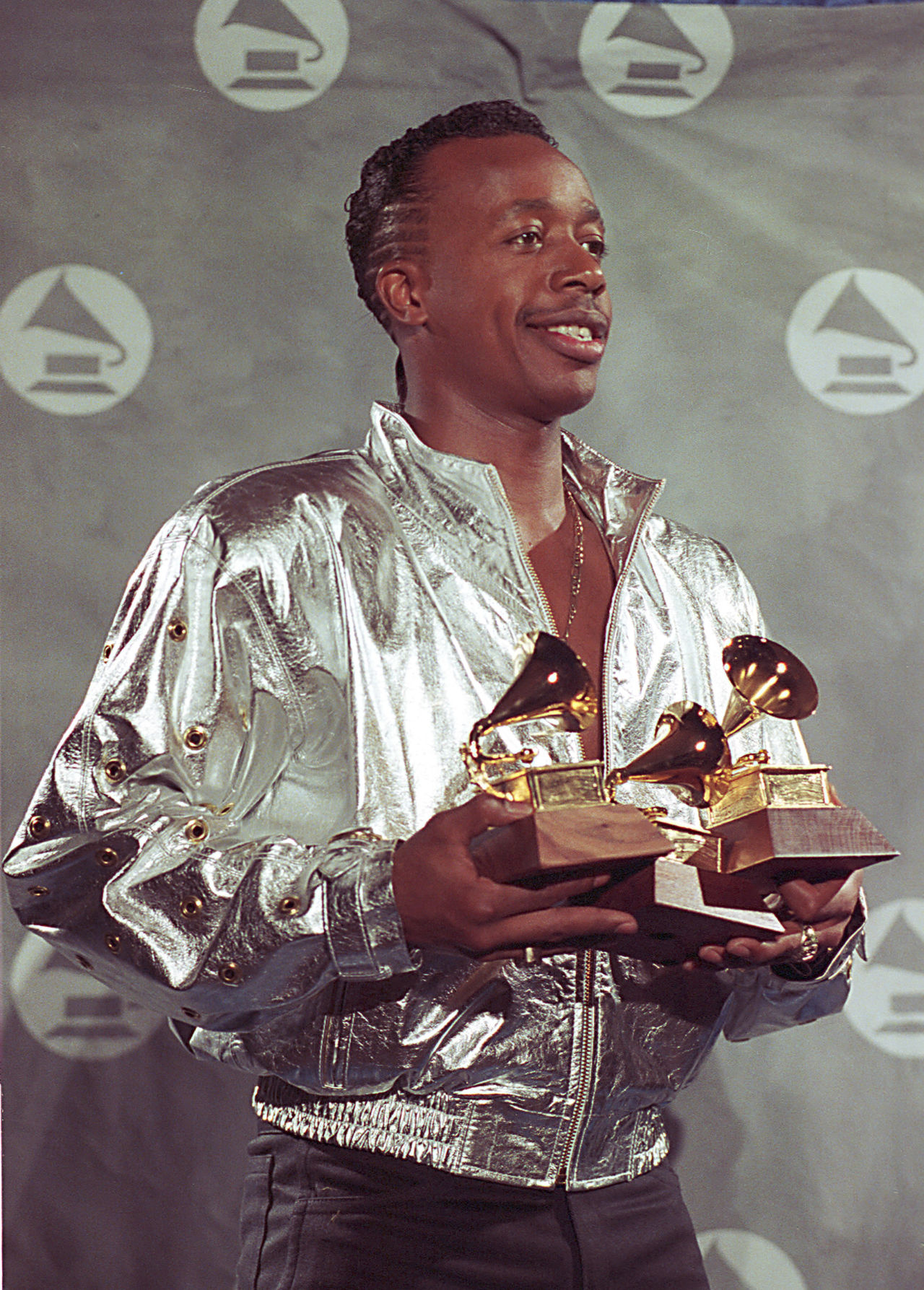 """Rap musician MC Hammer poses backstage with his Grammys during the 33rd annual Grammy Awards at New York's Radio City Music Hall, Wednesday night, Feb. 20, 1991.  Hammer won in the categories of best rhythm and blues song and best rap solo performance for """"U Can't Touch This.""""  (AP Photo/Susan Ragan)"""